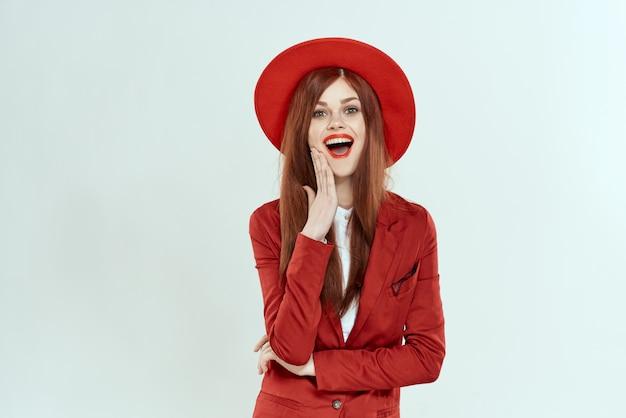 Belle femme rousse en costume et chapeau rouge, image de bureau élégante