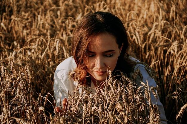 Belle femme rousse dans un champ de seigle. elle respire le parfum des oreilles fraîches. journée ensoleillée