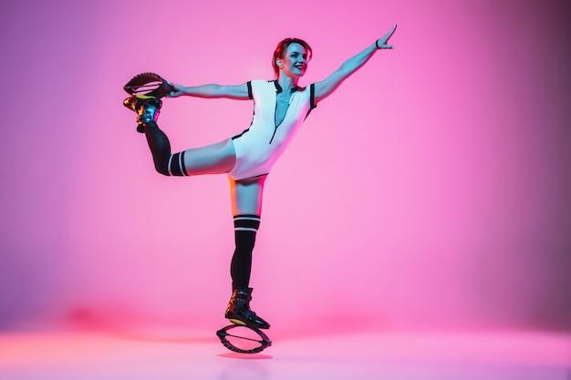 Belle femme rousse dans un vêtement de sport blanc sautant dans un kangoo saute des chaussures