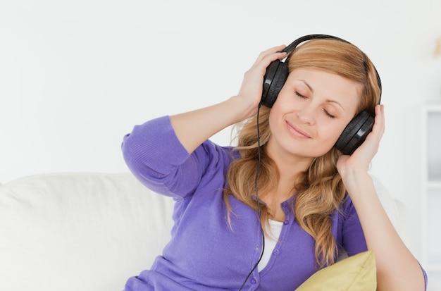 Belle femme rousse, écouter de la musique et profiter de l'instant tout en étant assis sur un canapé