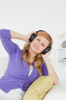 Belle femme rousse écouter de la musique et profiter de l'instant tout en étant assis sur un canapé