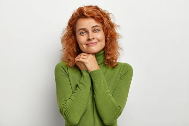 Belle femme rousse garde les mains jointes près du visage, regarde tendrement, sourit doucement, porte un pull vert, pose contre un mur blanc, a une peau saine, pas de maquillage. expressions faciales