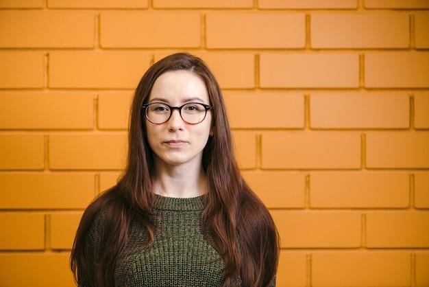 Belle femme rousse à lunettes sur mur de briques jaunes