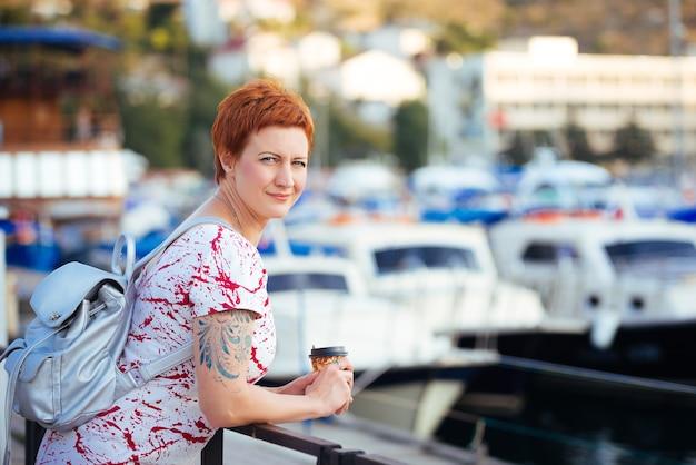Belle femme rousse à la mode, boire du café et profiter de vacances en mer dans le yacht club