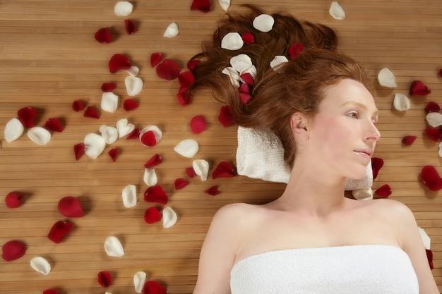 Belle femme rousse, pétales de rose sur les cheveux