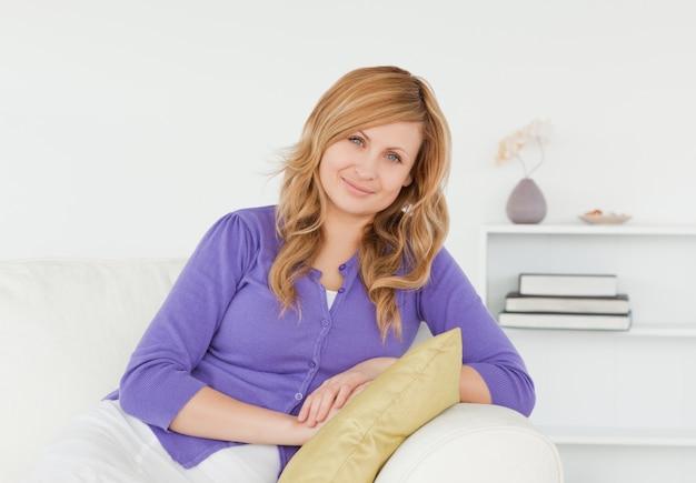 Belle femme rousse posant assis sur un canapé