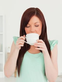 Belle femme rousse prenant son petit déjeuner dans la cuisine