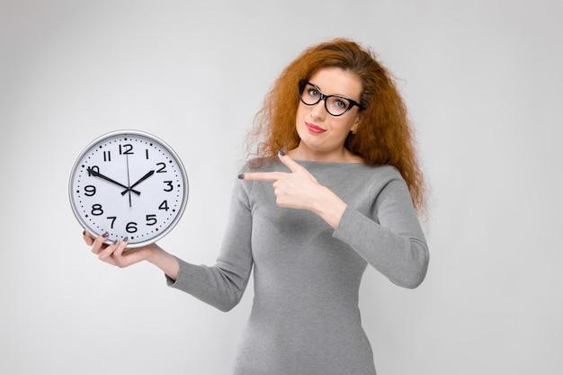 Belle femme rousse en tenue grise tenue d'horloge