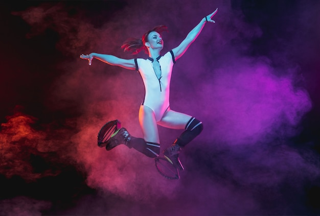 Belle femme rousse en tenue de sport sautant dans un kangoo saute des chaussures isolées sur fond de studio dégradé sombre dans une fumée éclairée au néon. mouvement actif, action, forme et bien-être. modèle élancé.