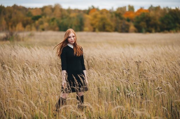 Belle femme rousse vêtue d'une robe noire se promène sur un champ en automne.