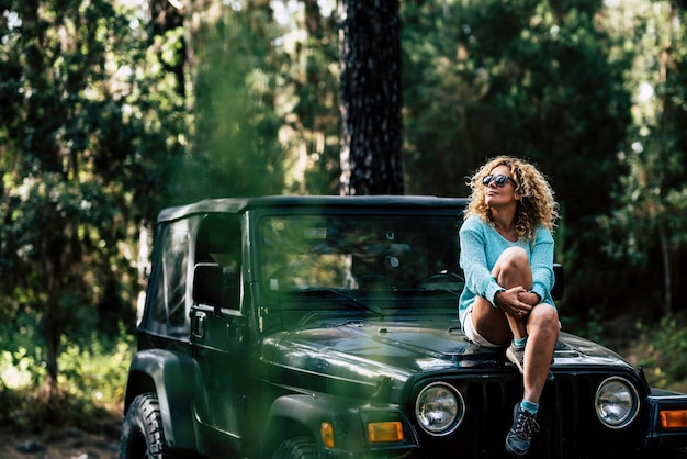 Belle femme s'asseoir sur la voiture tout terrain et profiter de la nature autour