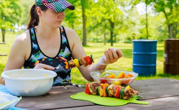 Belle femme s'habille sur des brochettes de shish kebab