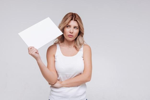 Belle femme s'interroge sur quelque chose tout en tenant une feuille de papier vierge