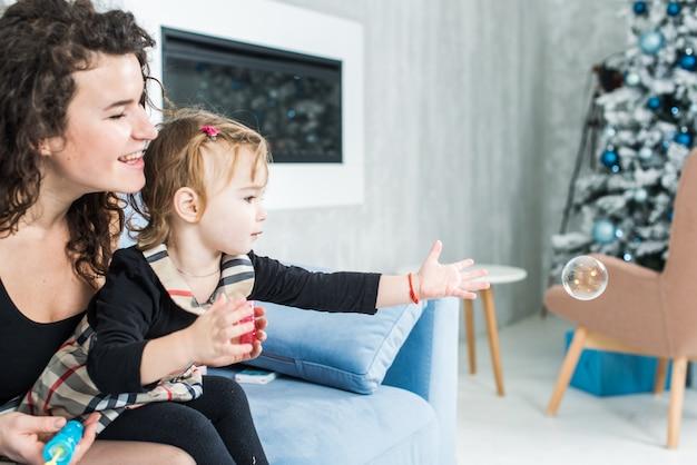 Belle femme et sa petite fille mignonne soufflent des bulles de savon