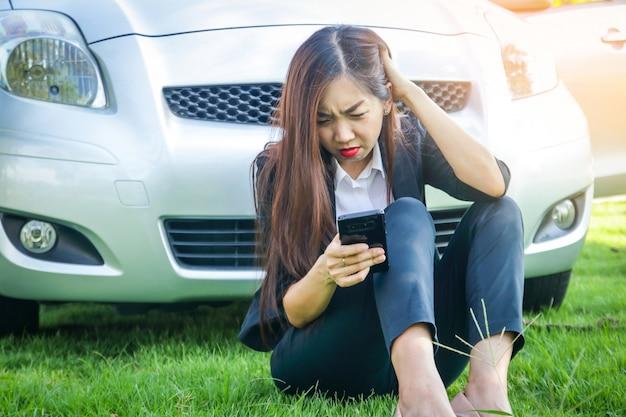 Belle femme, sa voiture est cassée elle s'est assise avec le téléphone pour obtenir de l'aide.