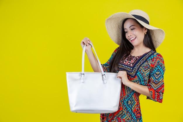 Belle femme avec un sac dans le jaune