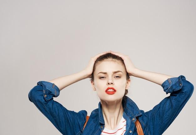Belle femme avec sac à dos vêtements modèle étudiant fond gris. photo de haute qualité