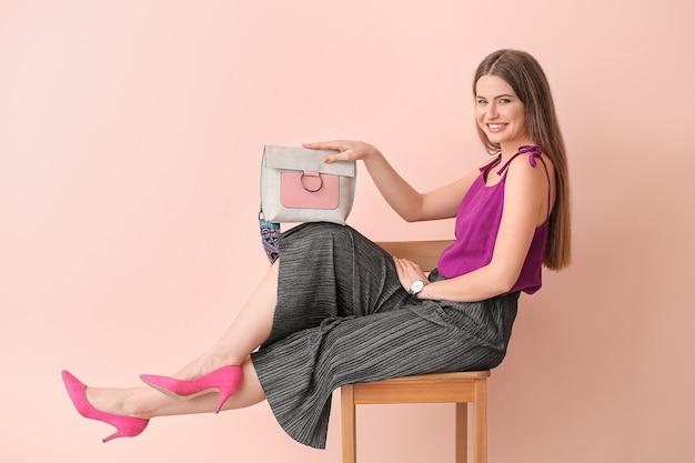 Belle femme avec un sac élégant assis sur une chaise près du mur de couleur