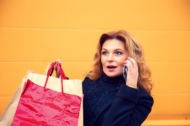 Belle femme avec des sacs parlant au téléphone.
