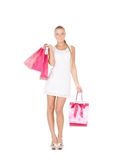 Belle femme avec des sacs à provisions sur blanc