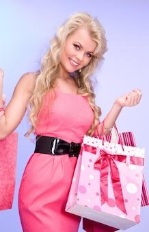 Belle femme avec des sacs à provisions sur bleu