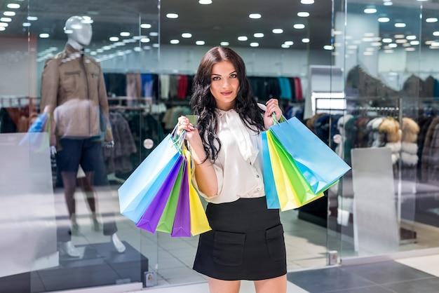 Belle femme avec des sacs à provisions debout dans un centre commercial