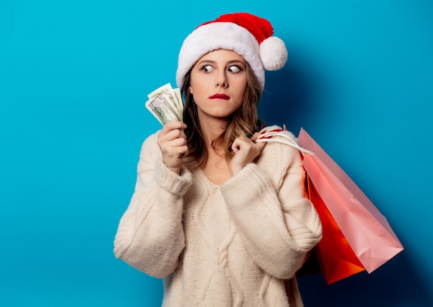 Belle femme avec des sacs à provisions et horloge d'argent sur le mur bleu