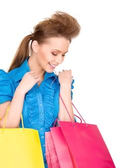 Belle femme avec des sacs à provisions sur mur blanc