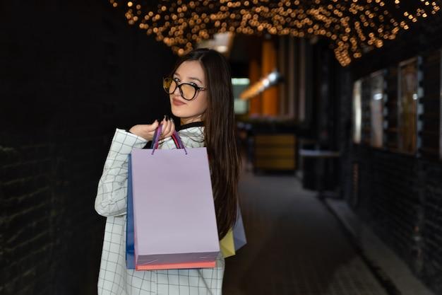 Belle femme avec des sacs à provisions regarde par-dessus son épaule. achats réussis.