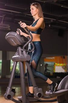 Belle femme à la salle de gym exerçant sur une machine