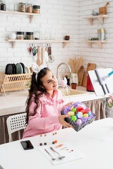 Belle femme saluant ses amis en ligne, célébrant pâques