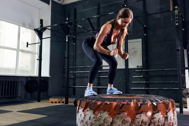 Belle femme sautant sur un énorme pneu dans crossfit gym
