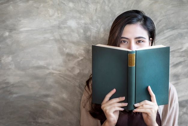 Belle femme se cache le visage derrière un livre vert tout en regardant la caméra.