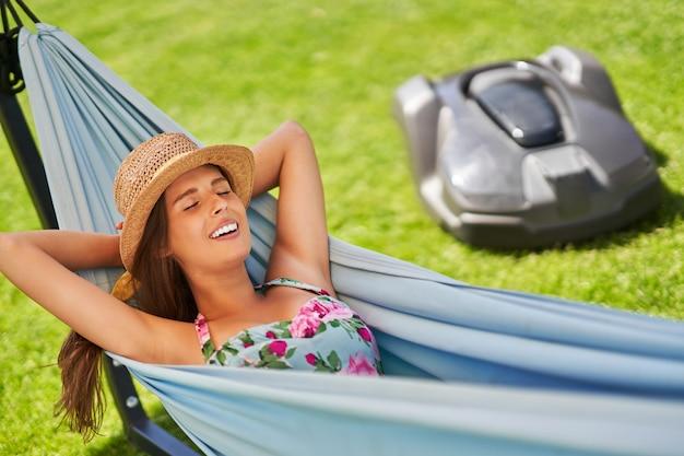 Belle femme se détendre dans un hamac profitant du temps libre grâce à automower
