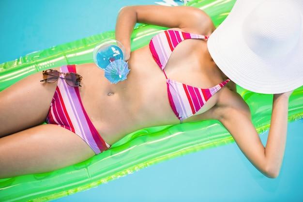 Belle femme se détendre sur un lit d'air en piscine caca