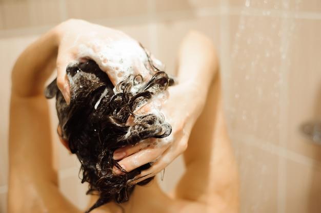 Belle femme se laver les cheveux avec du shampooing