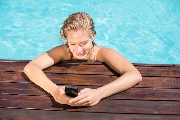 Belle femme se penchant sur le bord de la piscine et en tapant un message texte
