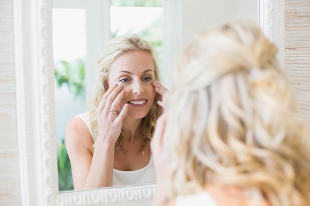 Belle femme se regardant dans le miroir de la salle de bain