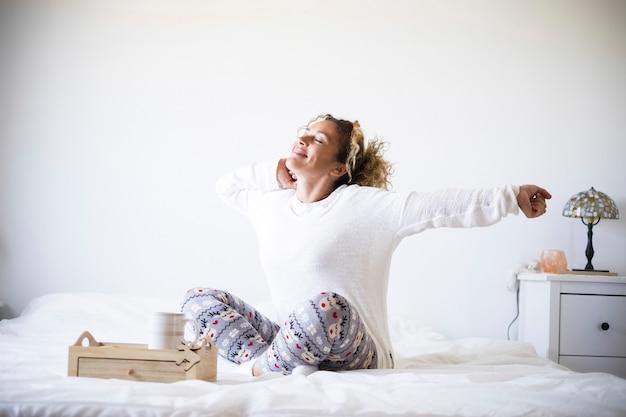 Belle femme se réveille le matin et prend son petit-déjeuner au lit - vie de chambre pour les personnes en bonne santé se réveillant et se préparant à commencer une nouvelle journée - image blanche et arrière-plan avec des gens