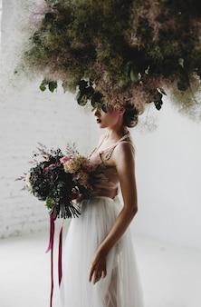 Belle femme se tient avec un bouquet parmi le linge suspendu dans la chambre