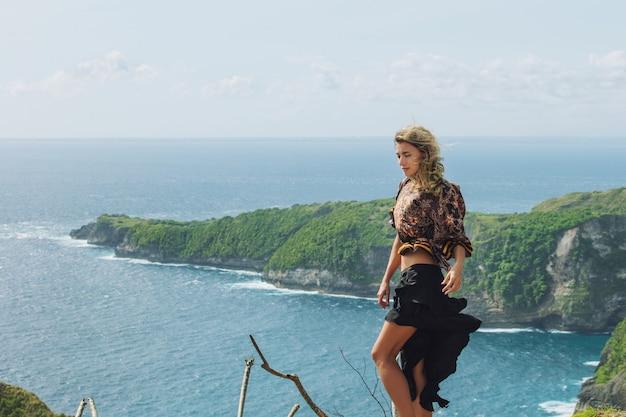 La belle femme se tient sur une falaise sur le fond de la mer et des roches dans un jour venteux