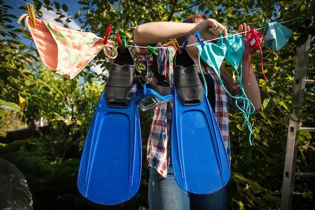 Belle femme séchant des palmes et un masque de plongée en apnée sur une corde à linge