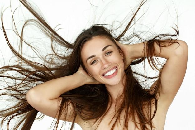 Belle femme secoue ses cheveux sur fond blanc
