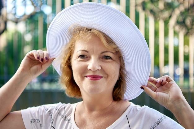Belle femme senior ans en chapeau blanc sourit en marchant à l'extérieur