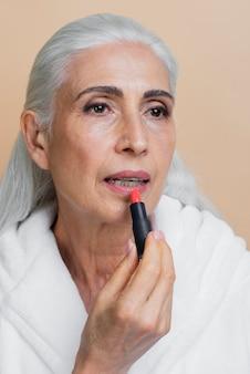 Belle femme senior appliquant du rouge à lèvres