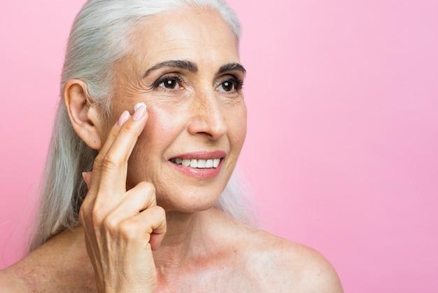 Belle femme senior appliquant un traitement de la peau
