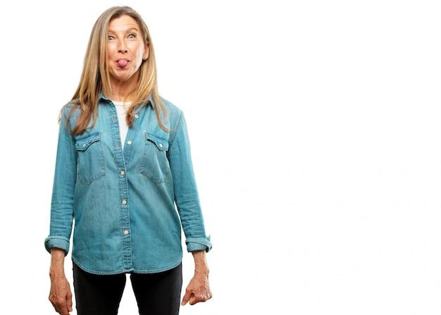 Belle femme senior blague, coller la langue avec une expression drôle, idiot et ludique, looki