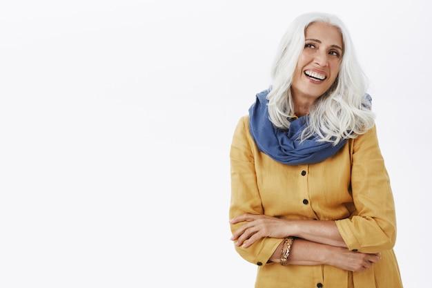 Belle femme senior coquette aux cheveux gris souriant et à la recherche dans le coin supérieur gauche