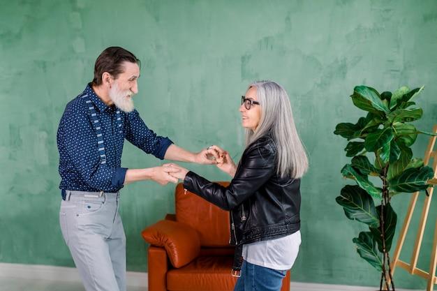 Belle femme senior élégante joyeuse avec de longs cheveux gris raides, dansant avec son beau mari barbu