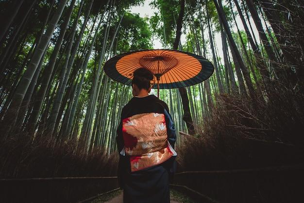 Belle femme senior japonaise marchant dans la forêt de bambous